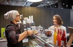 Man eller bartender med kakaportionkunden på kafét Royaltyfria Foton