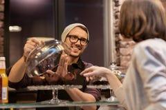 Man eller bartender med kakor som tjänar som kunden på kafét Arkivfoton