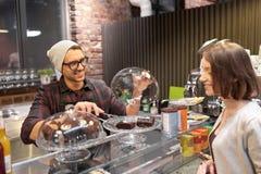 Man eller bartender med kakor som tjänar som kunden på kafét Arkivbild