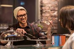 Man eller bartender med kakor som tjänar som kunden på kafét Royaltyfri Fotografi