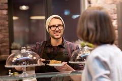 Man eller bartender med kakor som tjänar som kunden på kafét Fotografering för Bildbyråer