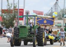Man eller bonde som kör en stor traktor i en ståta i lilla staden Amerika Arkivfoto