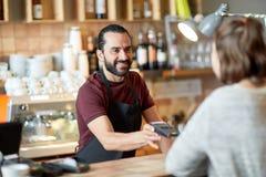 Man eller uppassare med kortläsaren och kunden på stången Arkivfoto