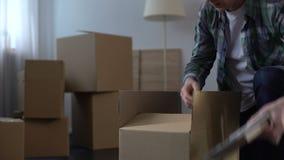 Man emballagesaker som är rörande ut från huset, arbets- flyttning utomlands, livändringar arkivfilmer