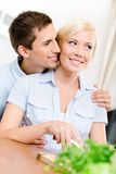 Man embraces girl while she is cooking Royalty Free Stock Photo