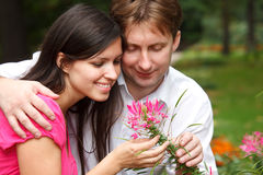 Man embraces girl showing it flower. Stock Image