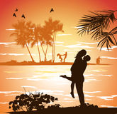 Man embraces woman on the shore of the beach at sunset Royalty Free Stock Images