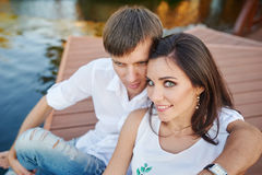 Man embraces woman sitting on a pier at the river bank Stock Images
