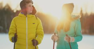 A man embraces a woman standing in the woods at sunset after a winter walk on skis. St. Valentine`s Day. Romance and stock video