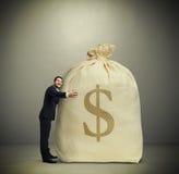 Man embracing big bag with money Stock Photos