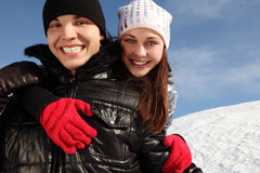 Man embracing girl, smiling and looking at camera. Young man embracing girl from back, smiling and looking at camera, winter day Stock Photography