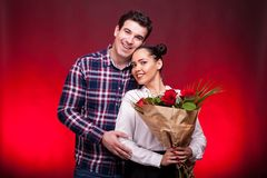 Man embracing her beautiful wife while she holds a roses bouquet Royalty Free Stock Photos
