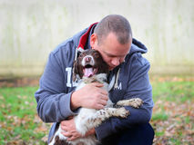 Man embracing his dog. Man embracing his new pet Spaniel dog at a rescue pound Royalty Free Stock Photo