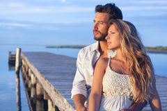 Man embracing his woman from behind on seaside background under Stock Image