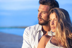 Man embracing his woman from behind on seaside background under Stock Images