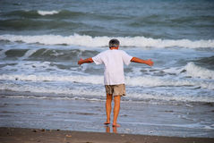 Man embracing the sea. Mature man flings open his arms to embrace the sea Royalty Free Stock Photo