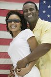 Man embracing woman, American flag in background Royalty Free Stock Photography