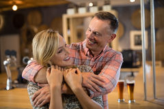 Man embracing woman from back in bar. Smiling men embracing women from back in bar Royalty Free Stock Photo