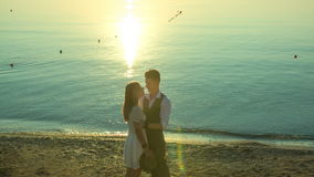 Man embracing a woman on the beach at sunrise stock video footage