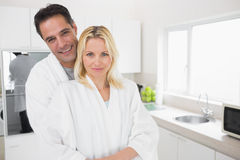 Man embracing woman from behind in kitchen Royalty Free Stock Images