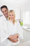 Man embracing woman from behind in kitchen Royalty Free Stock Image