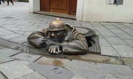 Man emerging from hole. Bronze street sculpture of man emerging from hole or drain. Bratislava Stock Image