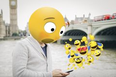 Surprised emoji on london. Man with emoji head surprised looking at the smartphone al london city royalty free stock photos
