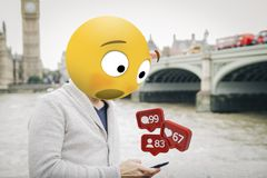 Surprised emoji on london receiving notifications. Man with emoji head surprised looking at the smartphone al london city royalty free stock photography
