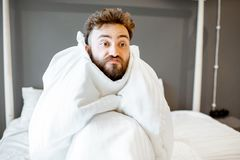 Man with emotional problems on the bed. Frustrated man with emotional insanity sitting on the bed covered with white sheets. Concept of insomnia or emotional royalty free stock photography