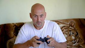 The man emotionally plays in the console. A man at the computer plays in the console stock video footage