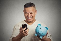 Man employee holding piggy bank looking at smart phone Royalty Free Stock Photos