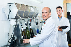 Man employee testing bottling equipment on facility Royalty Free Stock Images