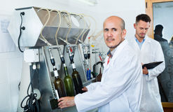 Man employee testing bottling equipment on facility Royalty Free Stock Image