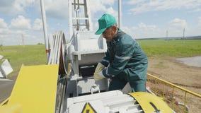 Man Employee Turns Round Metal Lever on Pumpjack. KAZAN, TATARSTAN/RUSSIA - AUGUST 22 2017: Middle-aged employee in green uniform turns round metal lever on stock video footage