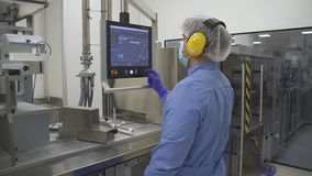 Man employee work with computer control production process in pharmaceutical factory.