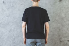 Man in empty black shirt back. Back view of man in casual black shirt. Retail concept. Mock up Royalty Free Stock Photography