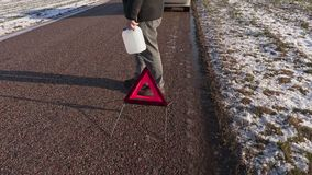 Man with empty can near warning triangle on the road stock video