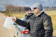 Man with empty can waiting for help near car Stock Image
