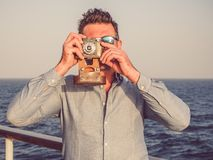 Man on the empty deck of a cruise liner. Attractive man holding a vintage camera on the empty deck of a cruise liner against a background of sea waves. Side view royalty free stock photo