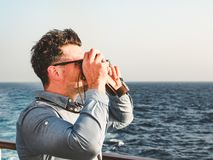 Man on the empty deck of a cruise liner. Attractive man holding a vintage camera on the empty deck of a cruise liner against a background of sea waves. Side view stock image