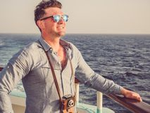 Man on the empty deck of a cruise liner. Attractive man holding a vintage camera on the empty deck of a cruise liner against a background of sea waves. Side view stock photography