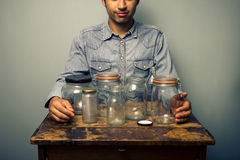 Man with empty jars at old desk Stock Image