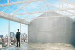 Man in empty loft interior room with city view, grey wal Stock Photography
