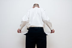 Man with empty pockets. Rear view of businessman holding out pockets to show they are empty, white background Royalty Free Stock Photo