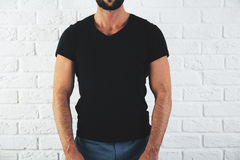 Man in empty shirt. Front view of man in casual black shirt with no print on white brick wall background. Mock up, Retail concept Royalty Free Stock Photos