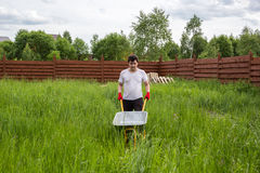 Man with empty wheelbarrow in the grass Stock Photo