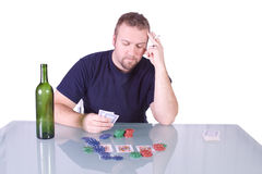 Man with an Empty Whiskey Bottle on a Poker Table Royalty Free Stock Photo