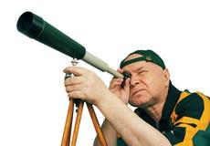 Man en astronom som ser till och med ett teleskop. Arkivbild