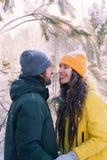 Man en de vrouw die zich dicht bij elkaar onder gevallen sneeuw de bevinden, besteden samen het concept van de de wintervakantie stock foto