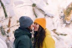 Man en de vrouw die zich dicht bij elkaar onder gevallen sneeuw de bevinden, besteden samen het concept van de de wintervakantie stock afbeelding